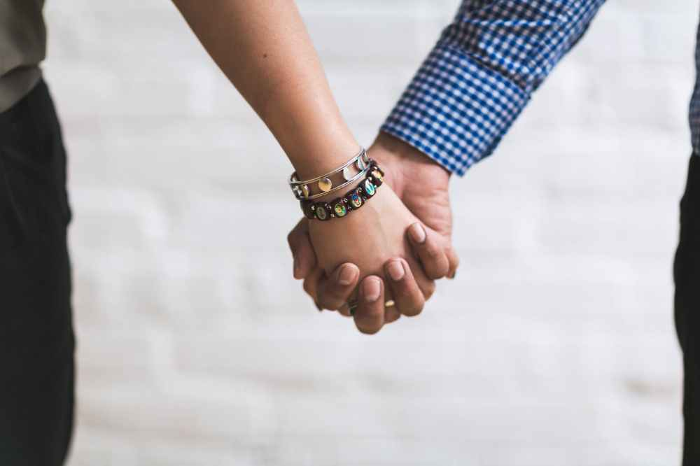 couple holding hands near white painted wall